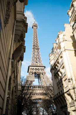 Photo of the Eiffel Tower in between buildings in Paris, France