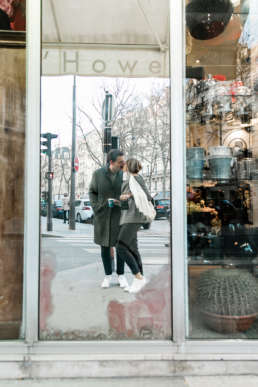 Photo of couple in mirror reflection kissing in Paris, France